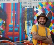 International mural artist, Eduardo Kobra, stands in front of his mural of Bob Dylan in downtown Minneapolis.